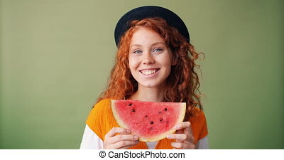 Portrait of girl holding watermelon smiling hiding face on...