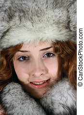 Portrait of girl in arctic fox cap - long haired young woman...