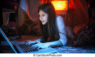 Portrait of girl in pajamas browsing internet before going to bed