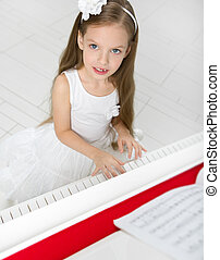 Portrait of girl in white dress playing piano