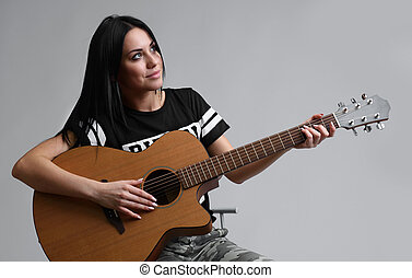 Portrait of girl playing on guitar