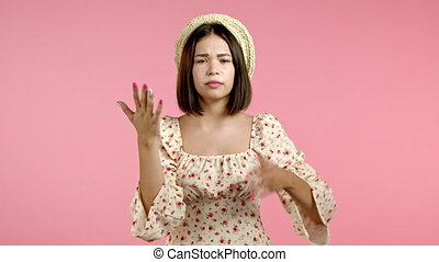 Portrait of girl, she exhales from heat or stuffiness, waves arms at herself. Heatstroke concept. Pink studio. Young tired woman is dissatisfied, unhappy