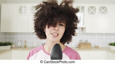 Portrait of girl singing in kitchen using spoon as microphone looking at camera.