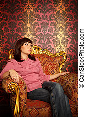 Portrait of girl sitting in armchair. Interior in retro ...