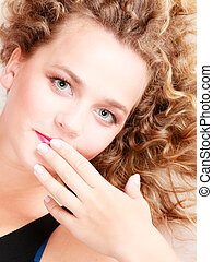 Portrait of girl with blond curly hair. Closeup of female face.