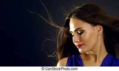 Portrait of girl with blowing black hair in wind. Slow motion.