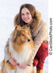 Portrait of girl with collie dog on snow landscape