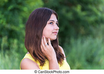 Portrait of girl with dark hair on the nature