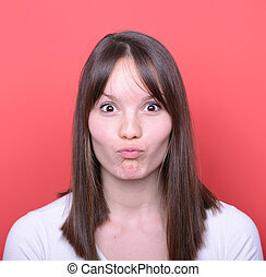 Portrait of girl with funny face against red background
