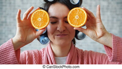 Portrait of girl with hair rollers holding oranges hiding...