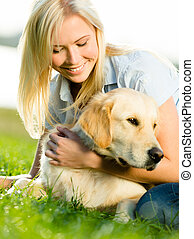 Portrait of girl with labrador on grass