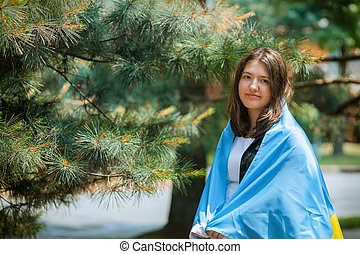 Portrait of girl with national a Ukrainian flag in the park outdoor