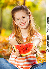 Portrait of girl with watermelon sitting in forest