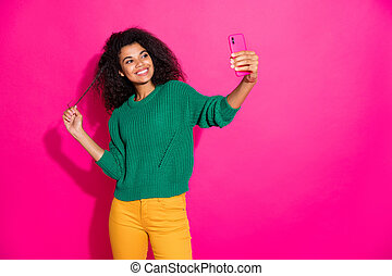Portrait of girlish positive afro american girl on autumn fall holiday take selfie feel content wear green stylish jumper yellow pants isolated over pink color background