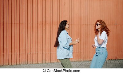 Portrait of attractive girls students dancing outside in city street having fun together wearing casual clothing and sunglasses. Joy, people and culture concept.