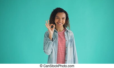 Portrait of glad African American girl showing OK hand...
