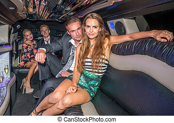 Portrait of glamorous young couple with friends sitting in limousine