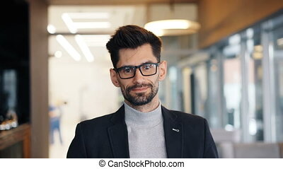 Portrait of good-looking mature businessman standing in cafe...