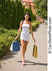 Portrait of gorgeous brunette shopper walking on the street with colorful shopping bags.