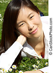 Happy smiling cute asian woman in park laying in grass
