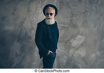 Portrait of gorgeous harsh masculine retired man in eyewear eyeglasses looking wearing hat coat isolated over gray background