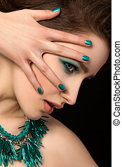 Portrait of gorgeous young woman with blue nails and eye makeup over black background