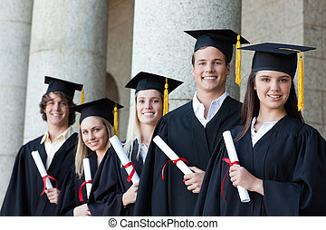 Portrait of graduates posing in single line with columns in...