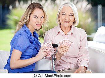 Portrait Of Granddaughter And Grandmother Playing Cards