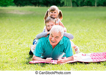 Portrait Of Grandfather And Grandchildren Lying On Grass