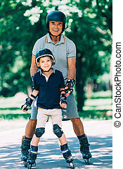 Portrait of grandfather and grandson roller skating in the...