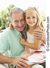Portrait Of Grandfather With Granddaughter Relaxing Together...