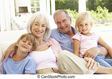 Portrait Of Grandparents With Grandchildren Relaxing...