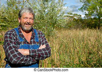 portrait of grey haired bearded farmer, wearing bib overalls & plaid shirt in meadow