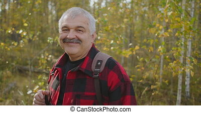 portrait of grey-haired tourist with moustache in forest at autumn day, man is smiling to camera, ecotourism, traveling and hiking at wild nature