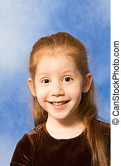 Portrait of grimacing redhead young girl with long hair