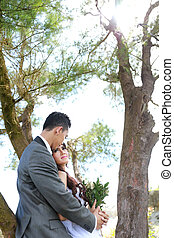 groom embracing his bride under tree