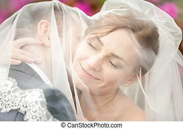 Portrait of groom kissing bride in neck under veil