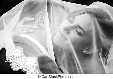 Portrait of groom kissing bride under white veil - Black and...