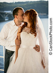groom kissing redhead bride at sunny day on riverbank
