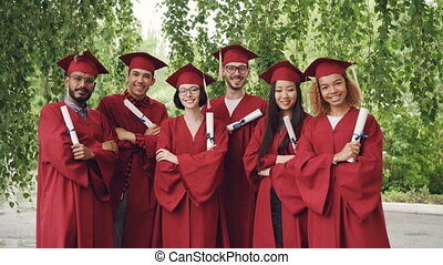 Portrait of group of graduating students holding diplomas and standing outdoors with arms crossed wearing gowns and mortar-boards, smiling and looking at camera.
