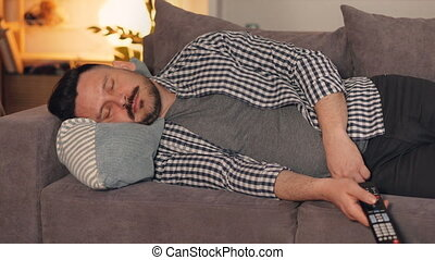 Portrait of guy in casual chothes sleeping on couch at home...