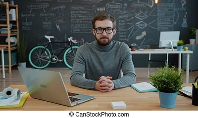 Portrait of guy in casual clothing and glasses at desk in ...