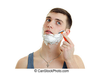 Portrait of guy with foam on his face who shaves his beard close-up