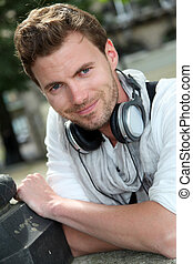 Portrait of guy with music headphones sitting in town