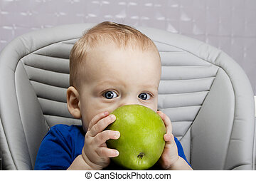 Portrait of handsome 9-month-old boy with a big green apple sitting in the baby chair