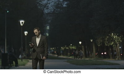 Portrait of handsome adult business man sending a text message while standing in the city street,business man reading messages,stylish brunette using cell phone at evening outdoors, park