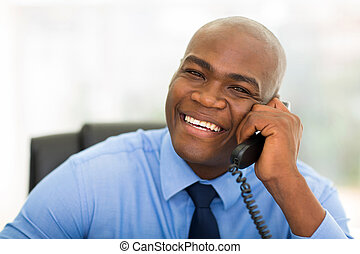 african office worker talking on telephone