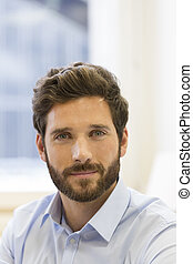 Portrait of handsome bearded man in office. looking camera