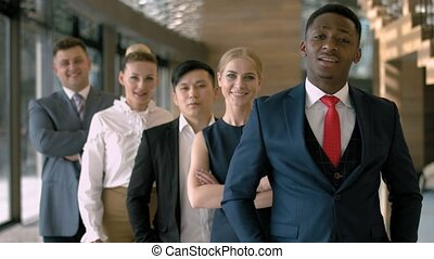 Portrait of handsome black business man with four employees...
