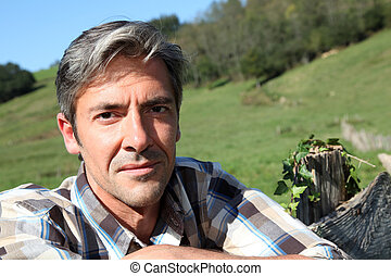 Portrait of handsome breeder leaning on fence